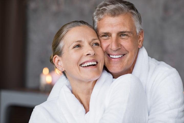 Laughing senior couple embracing at spa